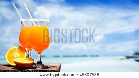 Two bocals of Tequila Sunrise cocktail on a beach table near ocen. Have a little break