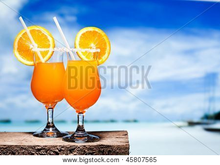 Two bocals of Tequila Sunrise cocktails on a beach table near ocen. Have a little break