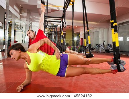 fitness TRX training exercises at gym woman and man side push-up workout