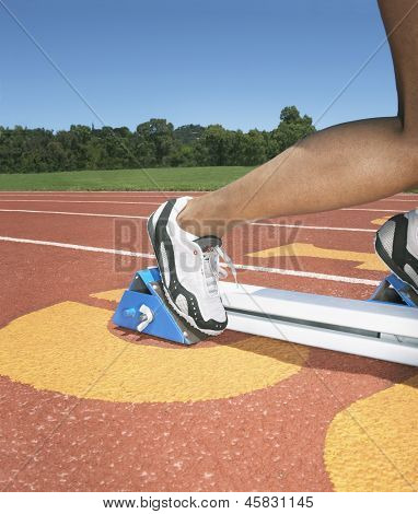 Side view of athlete's feet in starting blocks