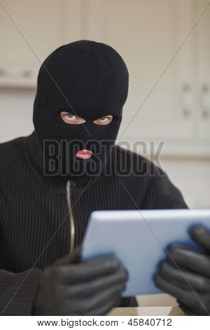 Suspicious burgler holding tablet pc in kitchen