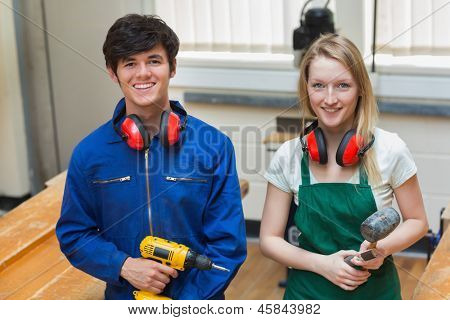 Two students standing in a woodwork class while holding a driller and a hammer