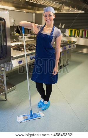 Smiling woman cleaning the kitchen floor in the restaurant
