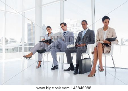 Business people sitting in waiting room with big windows