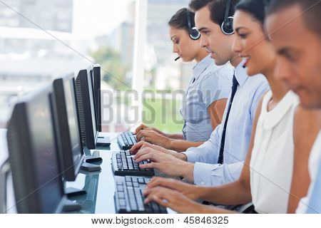 Call centre employees working on computers with their headset