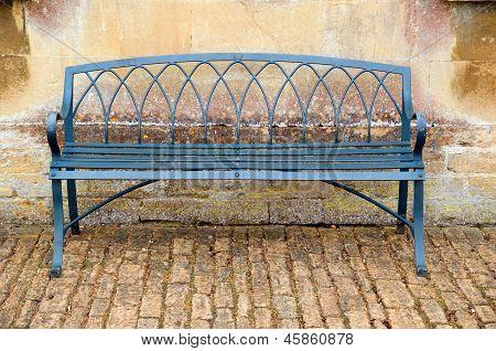 Empty bench on cobblestones