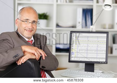Businessman Smiling With Computer On Desk