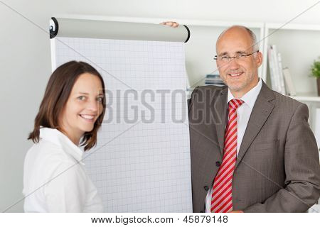Co-workers Standing Next To Flipchart
