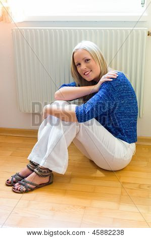 a young woman sits in front of a heater in the winter.