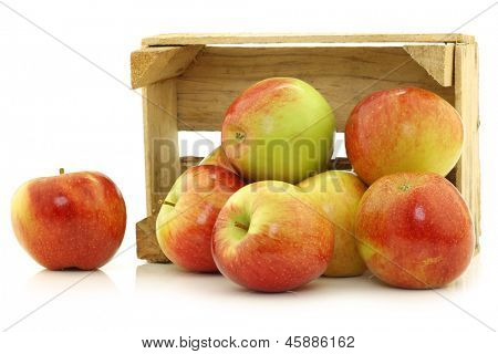 Fresh Braeburn apples in a wooden crate on a white background
