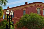 A red brick building with yellow trim stands out in Fernandina Beach City's historic downtown poster
