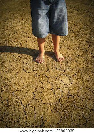 Little Boy Standing In Desert