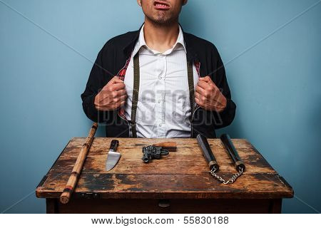 Dangerous Hitman Showing Off His Weapons on a table poster