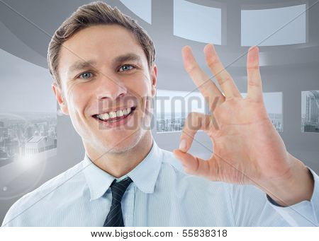Businessman showing ok sign against bright white room with windows