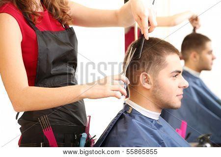 Beautiful girl hairdresser cut guy in beauty salon