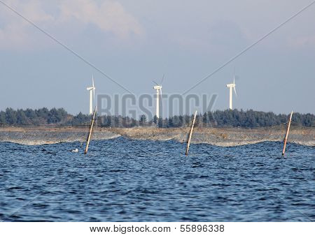 Offshore Fishing Net And Coast Line With Windmills