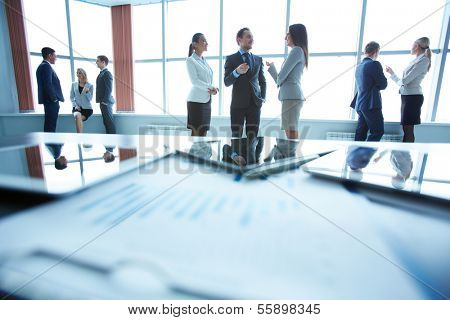 Business people interacting in office with workplace in front of them