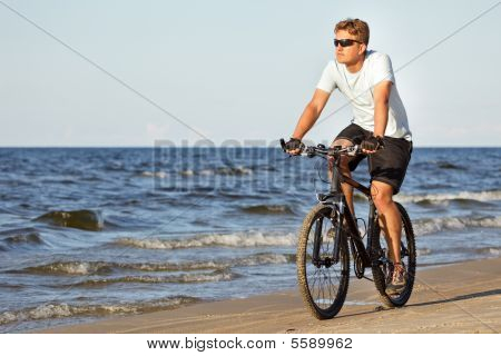 Man Riding Bicycle In Beach