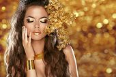 Fashion Beauty Girl Isolated on golden bokeh lights Background. Glamour Makeup. Gold Jewelry. Hairstyle. poster