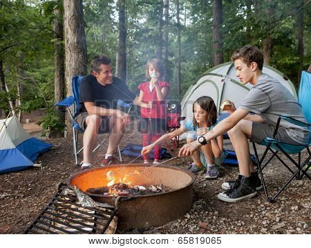 father camping with kids while kids roast marshmallows