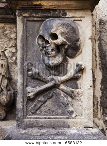 A grisly image of death grimacing with a skull and crossbones on a headstone in Kylemore Abbey in Edinburgh Scotland. poster