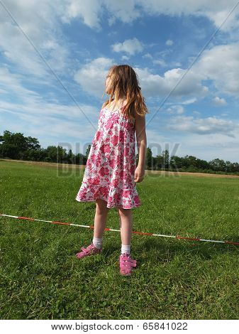 Girl, Blonde Looks On Cloudy Blue Sky, Around Her Field Greens.