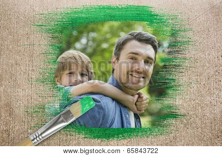 Composite image of father and son in the park with paintbrush dipped in green against weathered surface poster