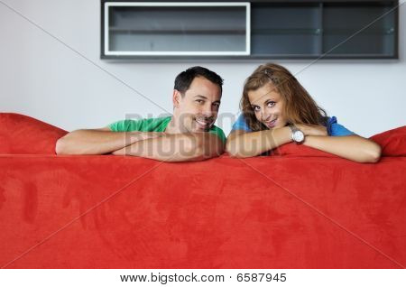 Happy Couple Relax On Red Sofa