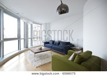 Modern Living Room With Floor To Ceiling Windows And Designer Furniture