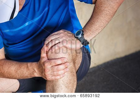 Male runner having problems in knee joint. poster