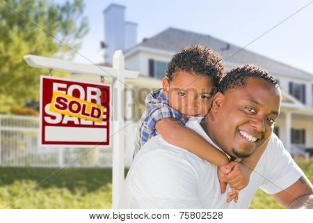 African American Father and Mixed Race Son In Front of Sold Home For Sale Real Estate Sign and New House.