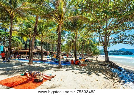 PHUKET, THAILAND- OCTOBER11, 2014: Tourists sunbathing on sand of Surin beach in shade of palms. Surin is beach retreat for discerning travelers and couples seeking relaxation in a serene setting