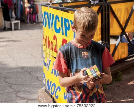 Smiling Yung Boy Trying To Solve An Intelligence Rubik's Cube