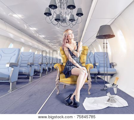Beautiful woman in the luxury armchair in an airplane cabin. Creativity concept