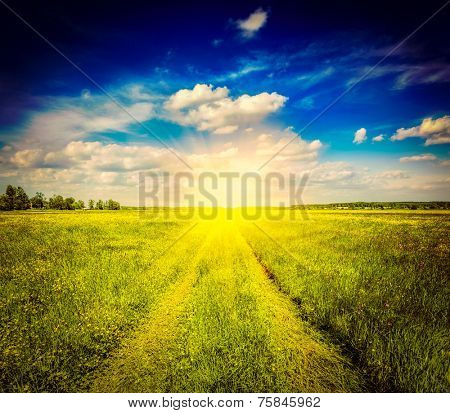 Vintage retro effect filtered hipster style image of spring summer background - rural road in  green grass field meadow scenery lanscape with blue sky