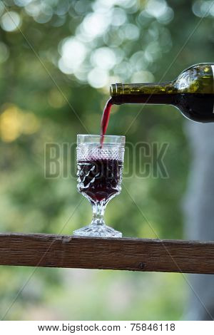 Red wine being poured into a crystal glass poster