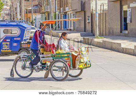 PUNO, PERU, MAY 5, 2014: Pedicab transporst local woman in traditional attire in city center