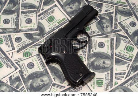 Black armed gun on US dollars background