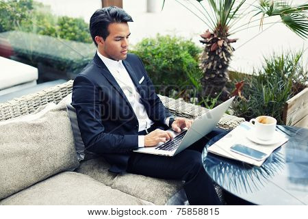 Confident man in suit typing on laptop computer keyboard working