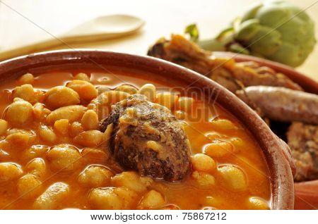 an earthenware bowl with potaje de judias y garbanzos, a traditional spanish legume stew