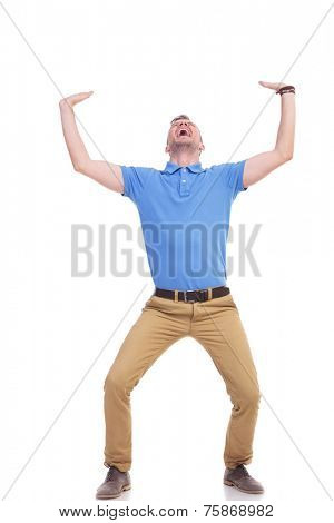 full length picture of a young casual man holding something imaginary above him with both hands and screaming out of difficulty. casual man being crushed. isolated on a white background