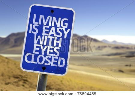 Living is Easy With Eyes Closed sign with a desert background