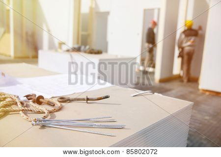 Building plan eye bolt and screws on plasterboard panels with workers in background poster