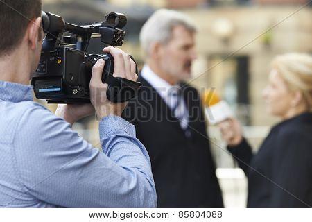 Cameraman Recording Female Journalist Interviewing Businessman Outdoors poster
