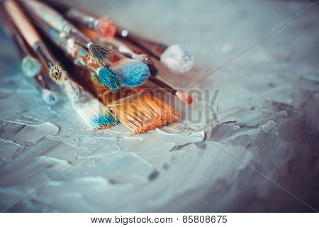 Paintbrushes On Artist Canvas Covered  With Oil Paints