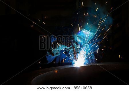 Welder worker is welding a big valve  body poster