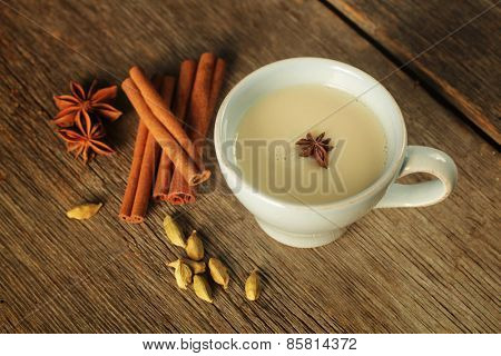 Blue cup with chai tea with cinnamon, anise and cardamom on a rustic background