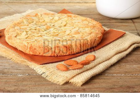 Dutch almond cake on a wooden table with slivered almonds on top. Also available in vertical.