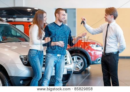 Sales consultant gives keys from new car to young couple