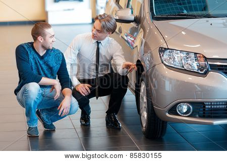 Sales consultant points to the wheel of  car talking
